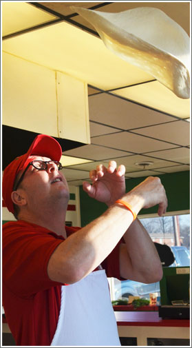 Picture of Dave Suiter tossing pizza dough in the air